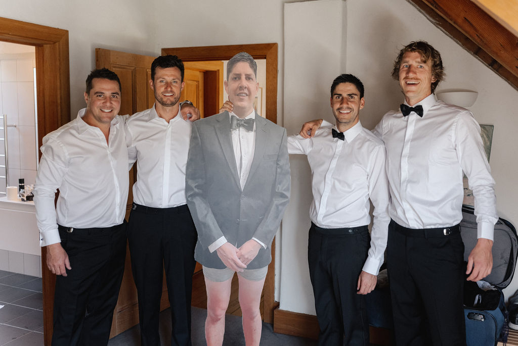 Groomsmen pose with a cardboard cut out of missing groomsman at Queenstown wedding in New Zealand