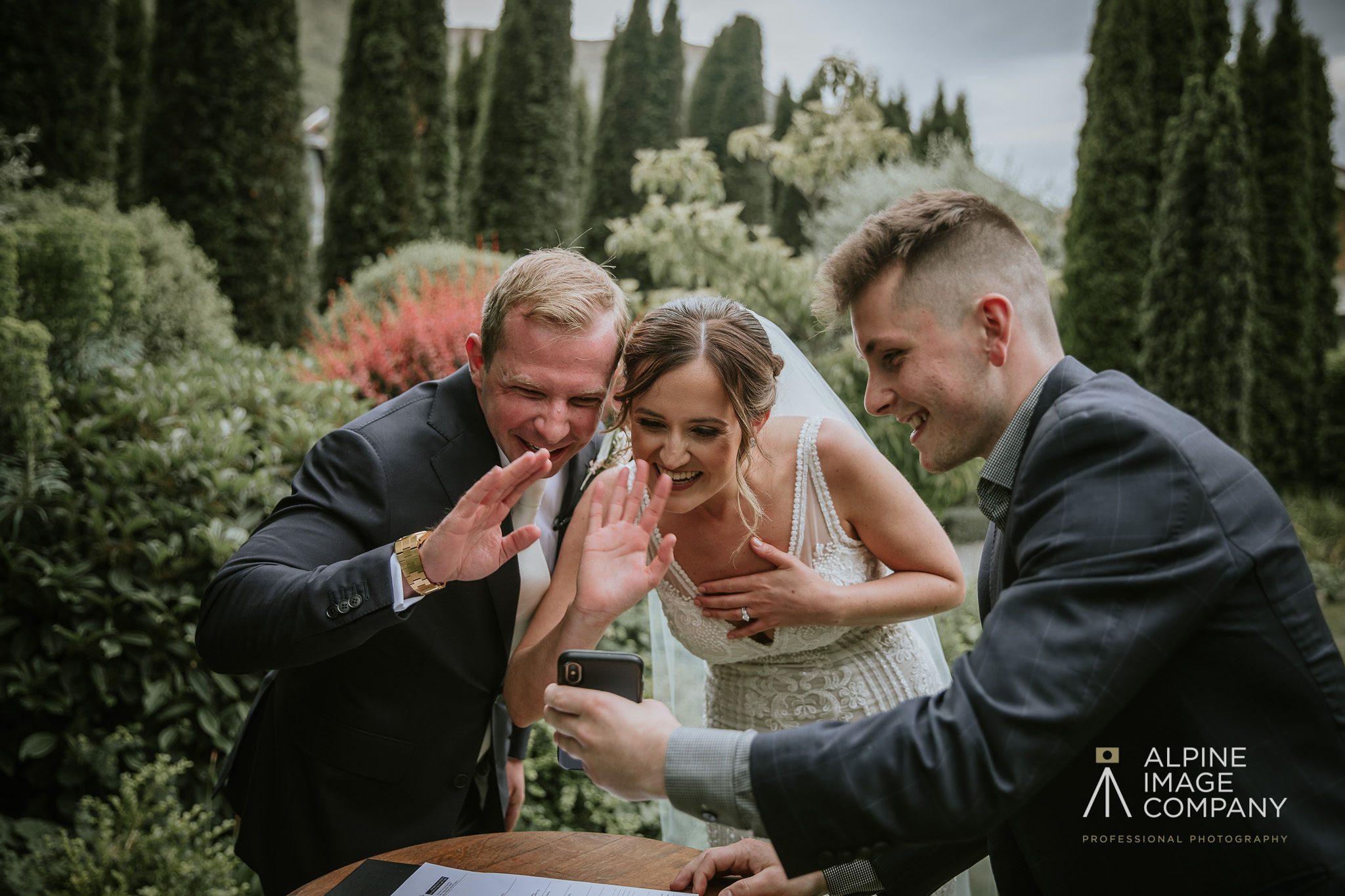 Bride and groom wave on a video call to missing family during wedding ceremony in Queenstown New Zealand